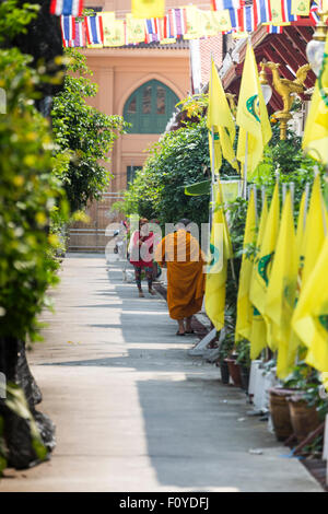 Buddhist monk walking down side street with flags, Bangkok, Thailand - Stock Photo