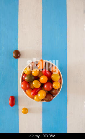 A bowl with multicolored fresh ecologic tomatoes on a rustic mediterranean style table. - Stock Photo