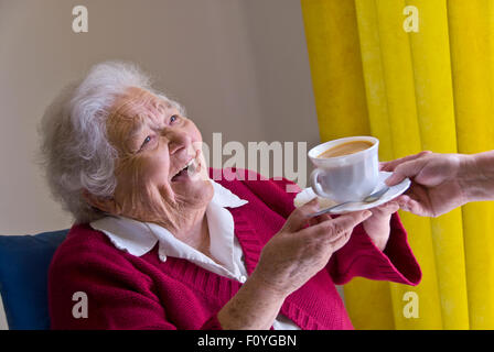 ELDERLY 90's HAPPY TEA CARE CARER HOME VISIT Happy laughing elderly lady receiving a cup of tea from carer nurse - Stock Photo