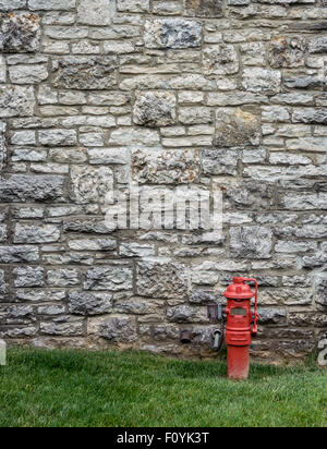 A red fire hydrant contrasts against an aged stone wall at a distillery along the bourbon trail - Stock Photo
