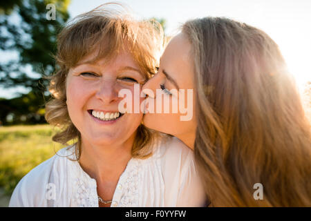 Teenage daughter kissing her mother outdoor in nature with sun in background, wide angle - Stock Photo
