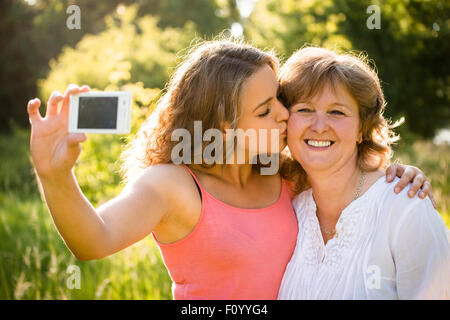 Adult daughter kissing her senior mother while taking selfie photo with mobile phone - Stock Photo