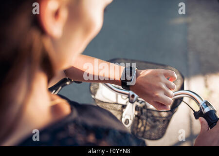 Woman with a bicycle looking at her smartwatch. Close up shot of female checking time on her smart wristwatch. - Stock Photo