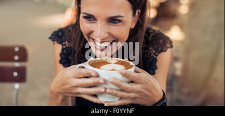 Close up shot of cheerful young woman drinking coffee at a cafe and looking away. Caucasian female enjoying a cup - Stock Photo