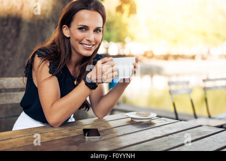 Portrait of beautiful young woman sitting at a table with a cup of coffee in hand looking at camera smiling while - Stock Photo