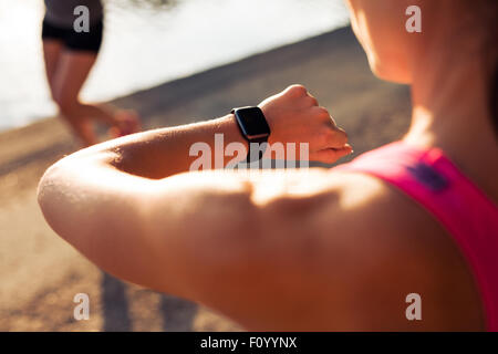 Close up shpt of sportswoman looking at her stopwatch. Jogger checking time on her smartwatch. - Stock Photo