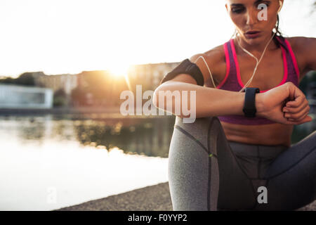 Beautiful young woman sitting outdoors using a smartwatch to monitor her progress. Caucasian female runner resting - Stock Photo