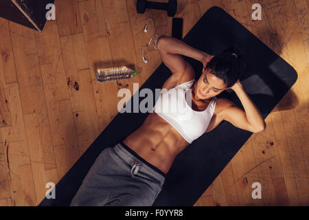 Sporty young woman lying on yoga mat doing sit-ups in gym. Top view of muscular woman doing abs crunches. - Stock Photo