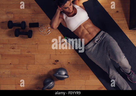 Sporty young woman lying on exercise mat doing sit-ups. Top view of muscular woman doing abs crunches in gym. - Stock Photo