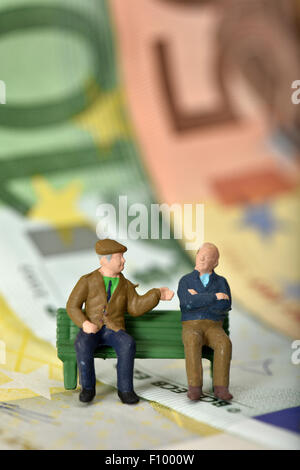 Pensioners on a bench, euro banknotes behind, symbolic image pension, private and state pension - Stock Photo