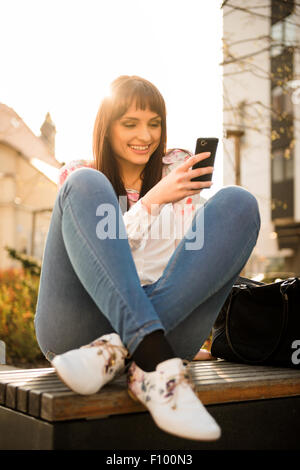 Young smiling woman looking to her phone in street with sun in background - Stock Photo
