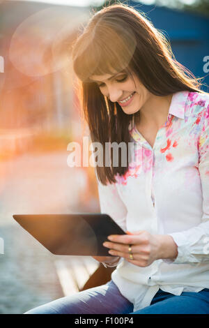 Young beautiful woman sitting on bench in street and browsing internet on tablet - Stock Photo