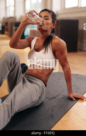 Fit young woman drinking water in the gym. Muscular woman sitting on exercise mat. Fitness female taking break after - Stock Photo