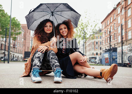 Two young women sitting on a skateboard with an umbrella. Female friends sitting together on street with skateboard - Stock Photo