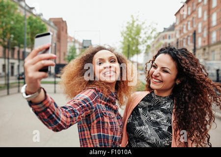 Two beautiful young women taking a picture together on city street. Young female friends taking a selfie using mobile phone, out Stock Photo