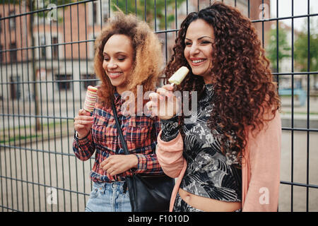Cheerful young girls eating candy ice cream. Two young women standing against a fence smiling, outdoors. - Stock Photo
