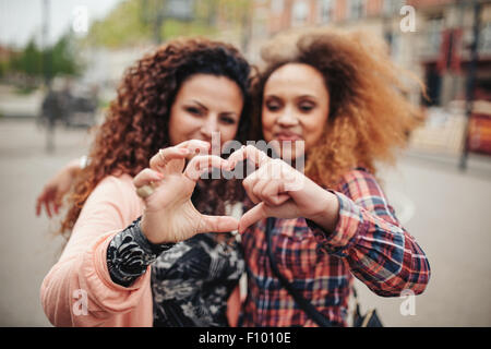 Happy young female friends making heart shape with hands and fingers. Two women standing together outdoors on city - Stock Photo