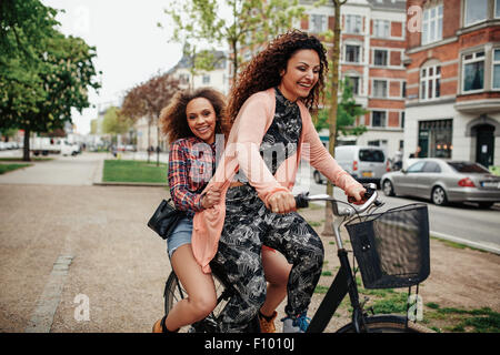 Cheerful young women enjoying bicycle ride on city street. Two young girls together riding on one bicycle. - Stock Photo