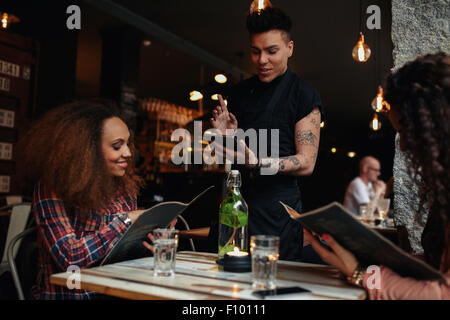 Happy young people sitting in restaurant reading menu card and giving orders to the male waiter, while waiter putting - Stock Photo