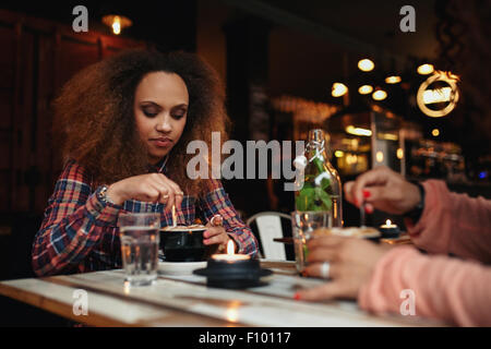 Shot of young african woman sitting at a restaurant stirring her coffee. Girl having coffee in a cafe - Stock Photo
