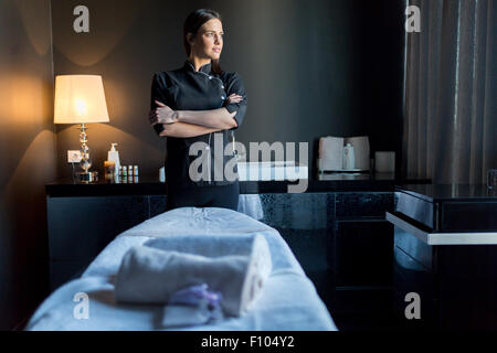 Massage therapist standing by massage table with hands crossed and looking outside the window - Stock Photo