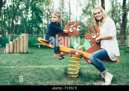 Mother and son playing in the playground and riding a seesaw - Stock Photo