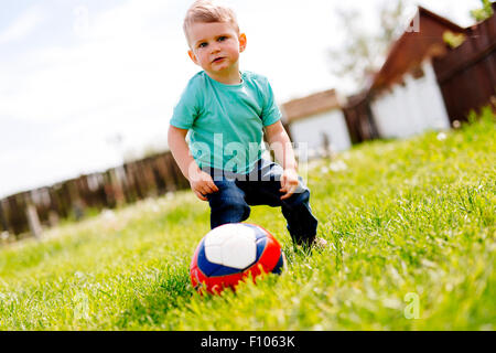 Adorable small boy playing with a soccer ball outdoors - Stock Photo