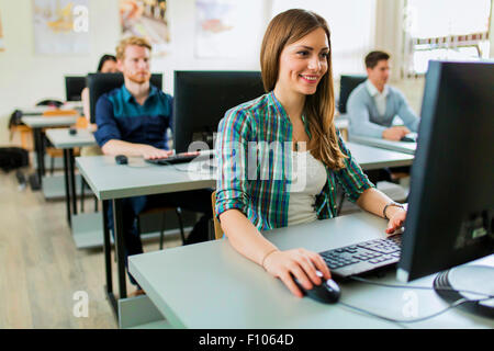 Young beautiful girl working on a computer in a classroom with her classmates in the background - Stock Photo