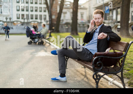 Businessman checking the time looking at his watch on a sunny day in a city park - Stock Photo