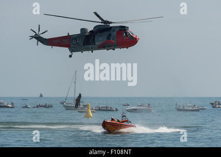 Royal Navy Sea King rescue demonstration with the RNLI at the Dawlish Air Show 2015 in its last year of active service. - Stock Photo