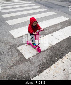 Child with kickbike at zebra crossing - Stock Photo