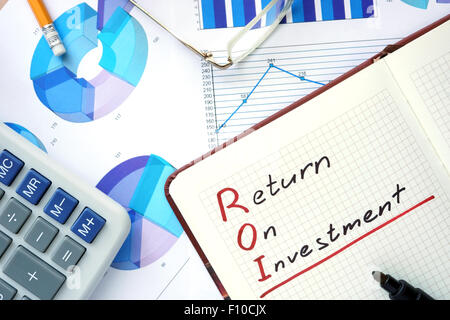 Notepad with word ROI return on investment concept and marker. - Stock Photo