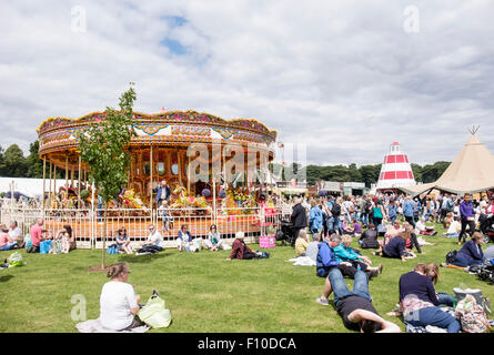 Visitors sitting in sunshine resting on lawns by Carousel at RHS Cheshire Flower Show, Tatton Park Knutsford Cheshire - Stock Photo