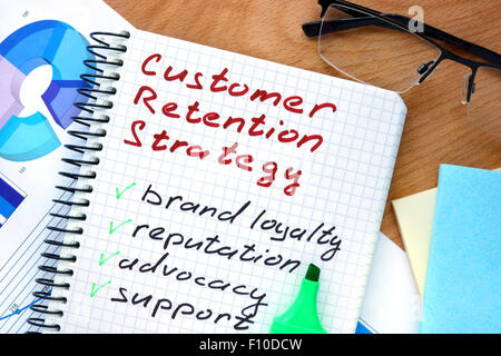 Notepad with words  customer retention strategies on a wooden background - Stock Photo