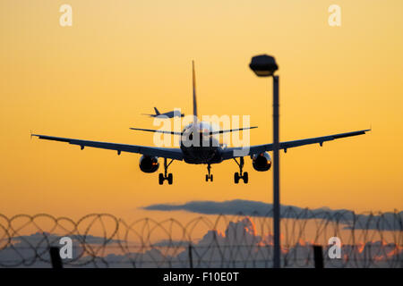 A British Airways Airbus A319 lands on Heathrow Airport's runway 27R as in the distance a British Airways A380 departs - Stock Photo