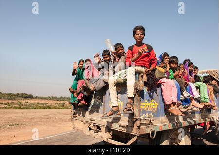 Rajasthan, India. Sawai Madhopur, near Ranthambore. Kids on the back of a truck. - Stock Photo