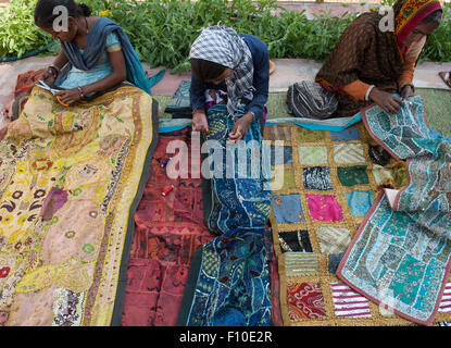 Rajasthan, India. Sawai Madhopur. Smiling local tribal women making traditional embroidered wall hangings. - Stock Photo