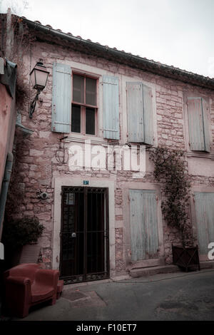 Outside of old french house with shutters and armchair washed out colour - Stock Photo