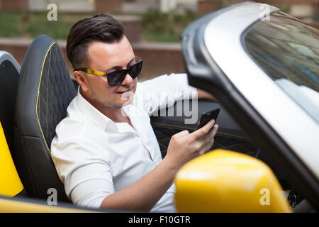 Driver man using smartphone in car - Stock Photo