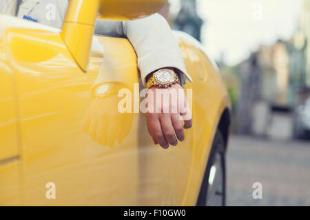 Closeup of man hand with golden watch in car - Stock Photo