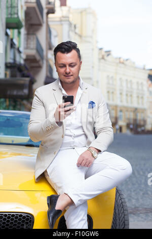Stylish man using smartphone near sport car - Stock Photo