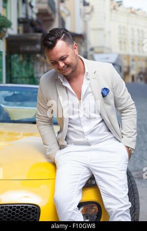 Stylish man smiling near sport car - Stock Photo