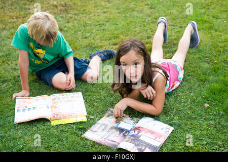 Kids reading together enjoying and reading a magazine laying on the grass outdoors - Stock Photo
