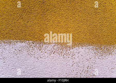 closeup of a rustic plastered wall painted in two colors, dark yellow and white, to use as a background - Stock Photo