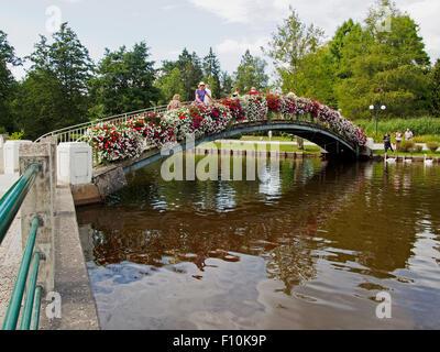 The floral bridge in the Casino Gardens in Bagnoles-de-l'Orne, Normandy, France - Stock Photo