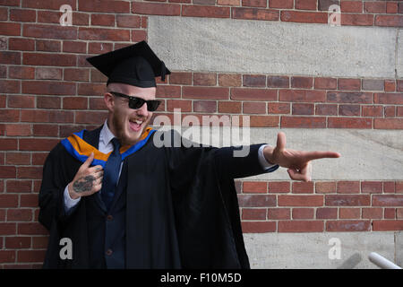 young male graduating student in cap and gown - Stock Photo