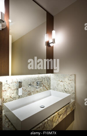A wide rectangular sink and a mirror in a modern bathroom - Stock Photo