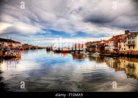 Whitby town harbour harbor coast coastal homes houses dramatic view scene sea pollution in water North Yorkshire - Stock Photo