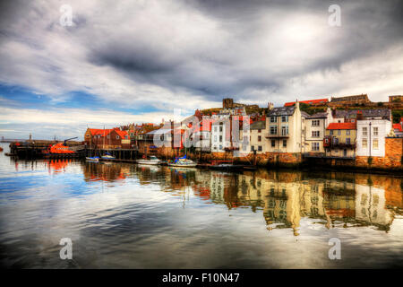 Whitby town harbour harbor coast coastal homes houses reflection in water dramatic view scene sea  North Yorkshire - Stock Photo