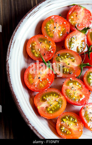 Organic chery tomatoes with black pepper and sea salt on plate, vegetarian appetizer - Stock Photo